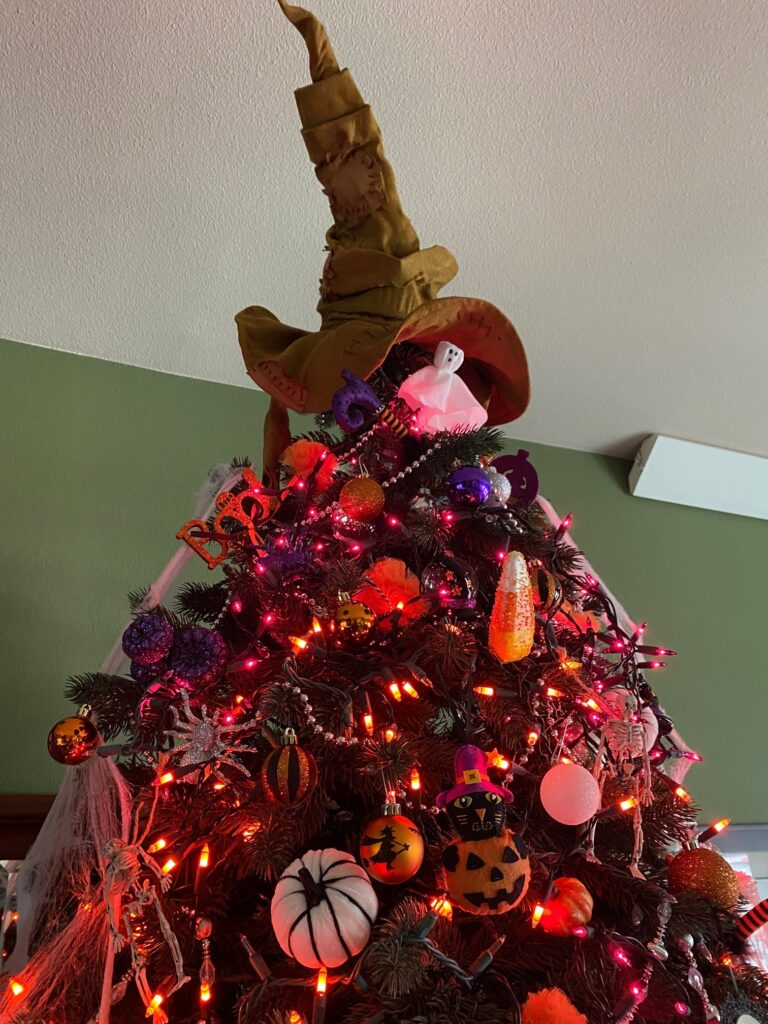 Christmas tree decorated for Halloween with Sorting Hat topper